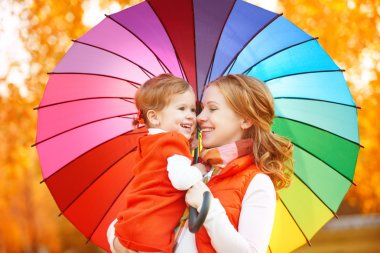 Happy family mum and child daughter with rainbow colored umbrell
