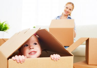 happy family moves into a new apartment. happy baby in a cardboa