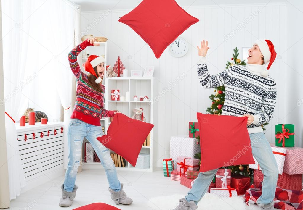 happy loving couple laughing and fighting on pillows on Christma