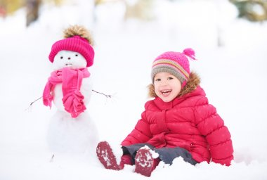 Happy child girl with a snowman on a winter walk