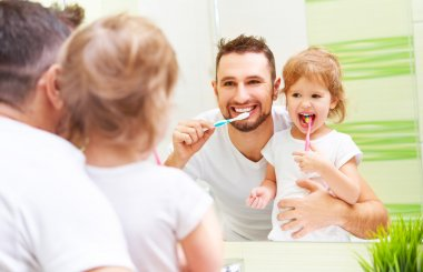 Happy family father and child girl brushing her teeth in bathroo