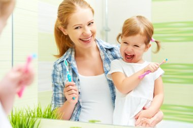 happy family mother and child girl cleans teeth with toothbrush