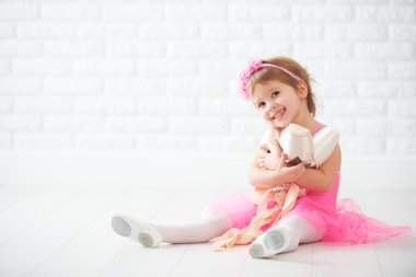 little child girl dreams of becoming  ballerina with ballet shoe