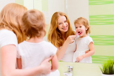 happy family mother and daughter child brushing her teeth toothb