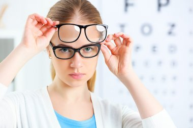 eyesight check. woman choose glasses at doctor ophthalmologist o
