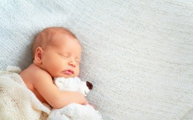 Cute newborn baby sleeps with toy teddy bear