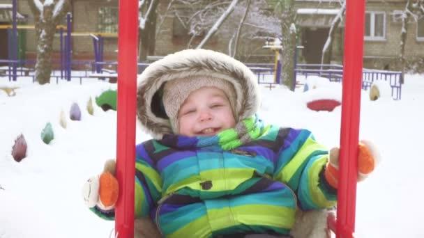 Kind auf Schaukel im winter