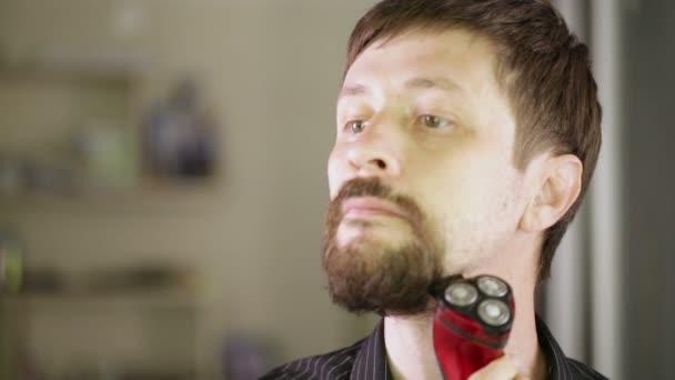 Muž holí vousy s elektrický holicí strojek