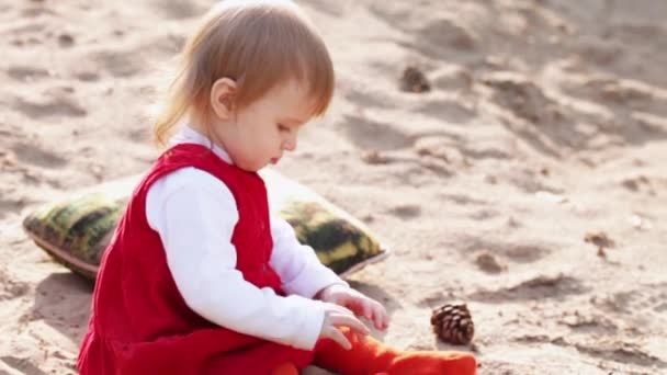 Little girl sitting on the sand