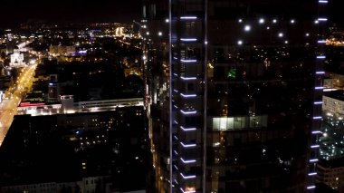Yekaterinburg aerial panoramic view at night of a modern skyscraper. Stock footage. Business center Vysotsky with glass facade and neon glowing lights.