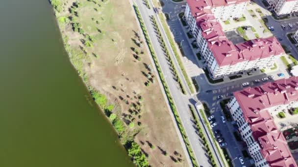 Aerial of summer landscape with a town, residential houses and a beautiful lake. Clip. View from the sky to a beautiful suburban town and a road along the shore of a large lake.