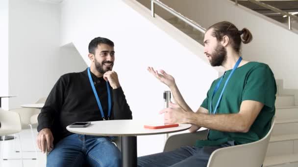 Geschäftsleute kommunizieren, während sie am Tisch sitzen. Medien. Zwei Männer mit Namensschildern unterhalten sich in einem Saal mit weißen Wänden und Treppen.