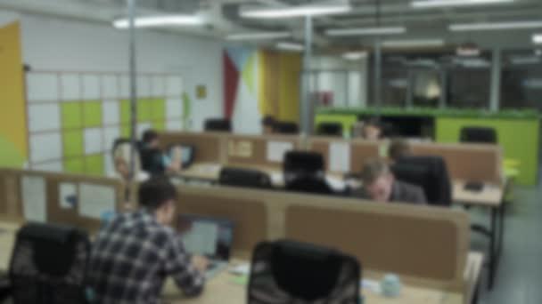 Rozmazaný pohled na zaměstnance pracující v zaneprázdněné kanceláři otevřeného plánu. Záběry ze skladu. Moderní kancelář rozmazané pozadí, velká korporace s pracovišti v otevřeném prostoru kanceláře.