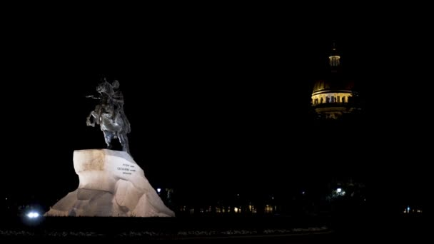 Socha Petra Velikého v noci v Petrohradě, Rusko. Akce. Památník bronzového jezdce na náměstí Senátu ve světle pouliční lampy na pozadí katedrály sv. Izáka