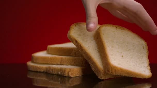 Man taking piece of bread. Stock footage. Close-up of man taking fresh slice of sliced bread on isolated background. Fresh white bread cut into square pieces