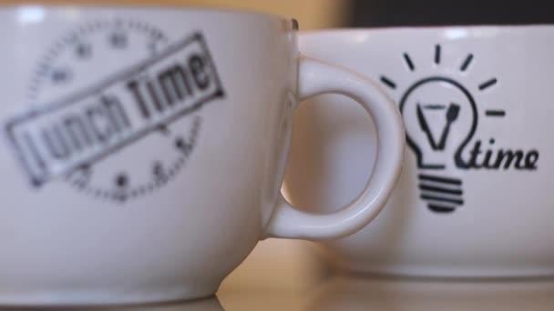 Detailní záběr dvou velkých bílých hrnků s nápisem na čas oběda a obrázkem žárovky. Koncept. Krásné hrnky na čaj nebo kávu, snídaně a teplé nápoje.
