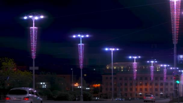 Schöne Laternen beleuchten die Stadt Straße in der Nacht auf schwarzem Himmel Hintergrund. Archivmaterial. Straßenlaternen mit bunter Beleuchtung, Stadtdekoration.