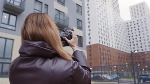 Žena fotí budovy s profesionální kamerou. Akce. Krásná fotografka točí vícepodlažní budovy. Zadní pohled na fotografku na pozadí obytných budov