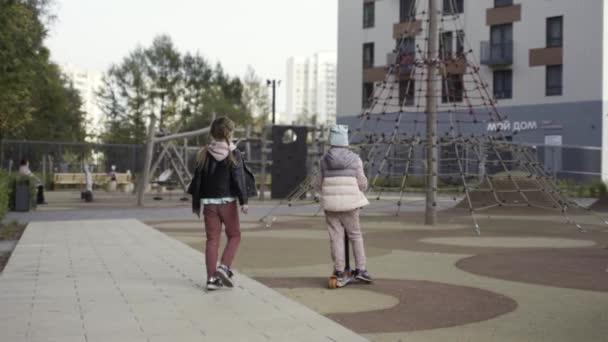 Zadní pohled na chlapce na skútru a dívku kráčející po dětském hřišti v blízkosti vysoké obytné budovy. Akce. Koncept šťastného dětství.