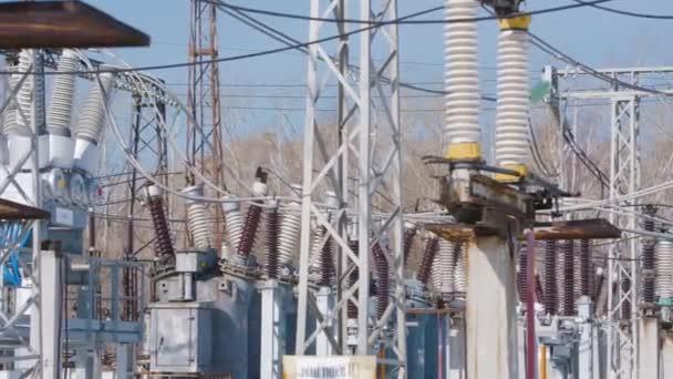 Viele Strommasten im Umspannwerk. Handeln. Elektrisches Umspannwerk mit leistungsstarker Ausrüstung und Transformatoren, die im Winter arbeiten. Winterklarer Tag im Elektrizitätswerk