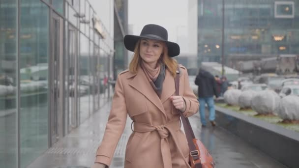 Woman walks through modern city in snow. Action. Stylish woman walks through business center of city in winter. Attractive woman walks confidently and smiles down street