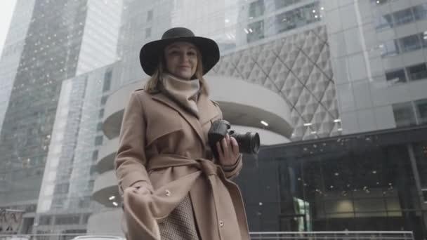 Atraktivní mladá blondýnka s kamerou v rukou na ulici. Akce. Elegantní fena v hnědém kabátě a černém klobouku s úsměvem pózuje v zimním dni na pozadí moderních budov