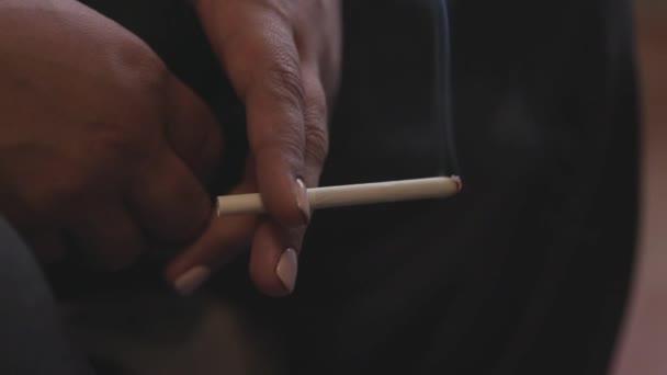 Nahaufnahme einer fünfzigjährigen Frau, die eine Zigarette raucht. Archivmaterial. Hände einer älteren Frau mit weißer Maniküre, die Zigarette raucht, Konzept der Müdigkeit.