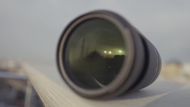 Fényképezőgép lencsék közeli felvétele a város és az ég homályos hátteréről. Felvétel. Új professzionális fényképezőgép objektívek bemutatása.