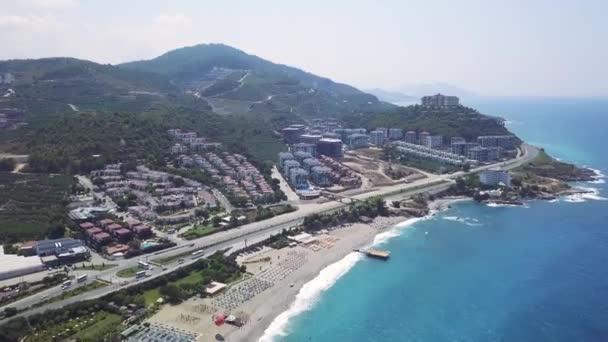 Ranní panoramatický výhled na moře a pláž z, letecké drone pohled. Klip. Moderní letní letovisko s dlouhým pobřežím a písečnou pláží, jižní město s dlouhou rovnou cestou.