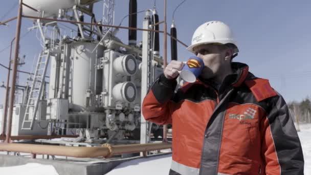Sibiř - Rusko, 02.16.2021: sebevědomý elektrikář stojící před transformátorem v elektrárně. Akce. Pracovník pije čaj nebo kávu z poháru s nápisem superman, koncept