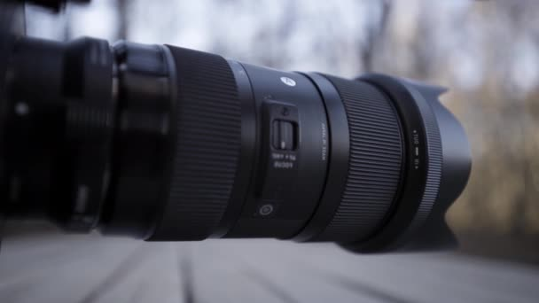 Close up side view of a black plastic camera lens on blurred background outdoors. Action. Demonstration of photographer equipment.