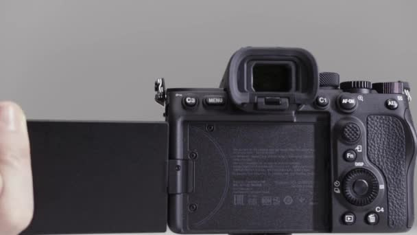 Close up of demonstration of a movable camera display. Action. Male hands turning professional camera screen isolated on grey background.