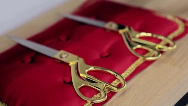 Arany olló közeledik a vörös párnán heverő hivatalos ceremóniákhoz. Videó. A nyitás és a pátosz fogalma.