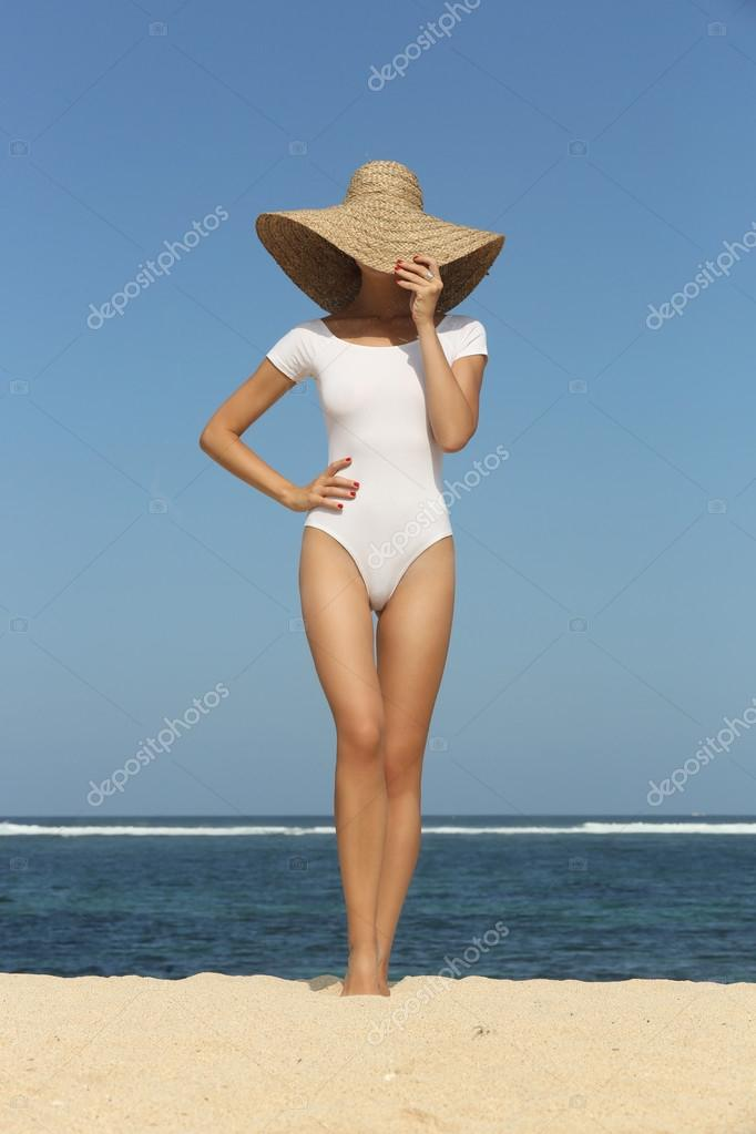 Girl on the beach wearing  big straw hat