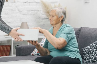 Elderly woman customer receives parcel box at home.