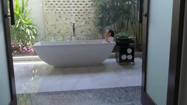 Portrét mladé ženy relaxující ve vaně, organická péče o pleť v luxusních hotelových lázních, pohoda a sebepéče