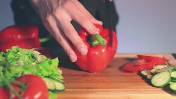 Chef schneidet rote Paprika auf Schneidebrett