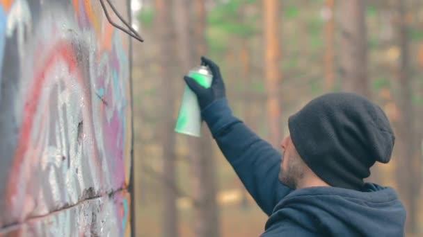 Mladistvý chlap kreslení graffiti pomocí stříkací plechovky