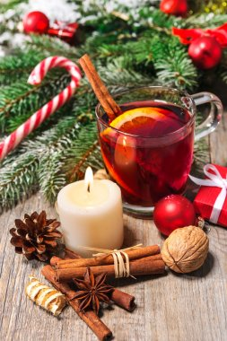 Glass of red mulled wine on table with with burning candle and christmas decorations stock vector
