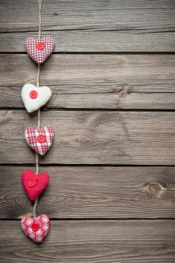Red hearts hanging over old wood background stock vector