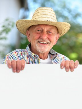 senior man with a straw hat holds a blank board