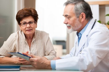 Doctor talking to his female senior patient