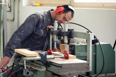 Carpenter working with wood in workshop