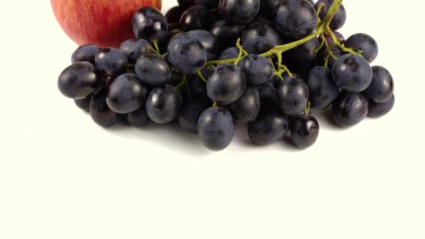 Black grapes and red apple on a white background