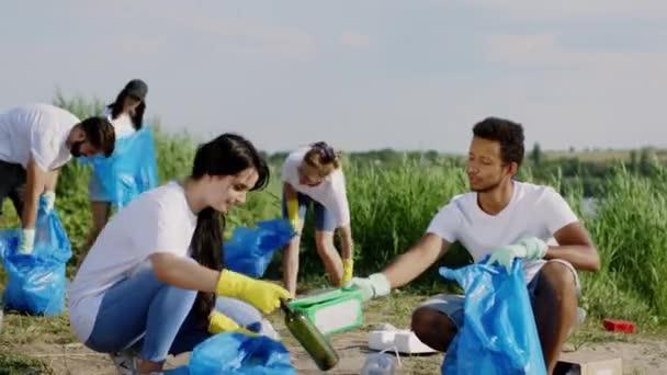 Vor der Kamera sammelt eine Gruppe charismatischer Typen freiwillig Müll vom Strand auf den blauen Plastiktüten