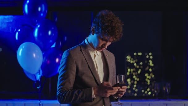 Szülinapi party ideje vonzó fickó öltönyben nézi át a telefont, miközben kezében egy pohár pezsgő élvezi a party hangulatát