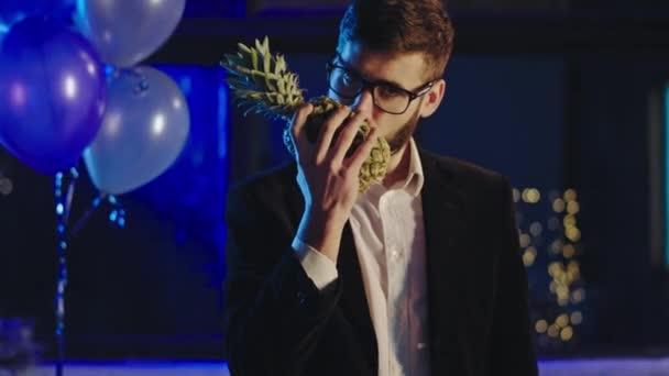 Egy fickó a partin öltönyben vesz egy ananászt és elkezd szaglászni és pózolni a kamera előtt jól érzi magát a partin.