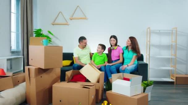 Attraktive Familie zog in ein neues Haus sie sind sehr aufgeregt genießen den Moment, während sie auf dem Sofa im Wohnzimmer lächelnd groß