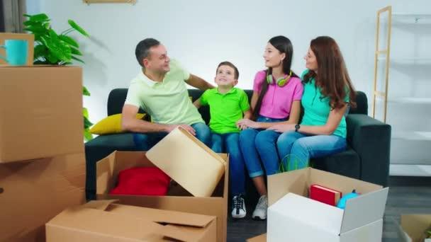 Vor der Kamera große charismatische Familie glücklich genießen den Moment in einem neuen Haus nehmen sie auf dem Sofa Platz und zeigen groß wie