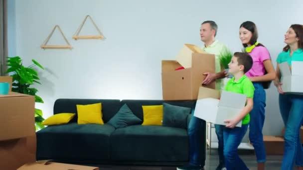 Aufgeregt große lächelnde Familie mit Kisten voller Sachen, die in ein neues Zuhause umziehen, stellen sie die Kisten auf den Boden und setzen sich auf das Sofa, um den Moment zu genießen